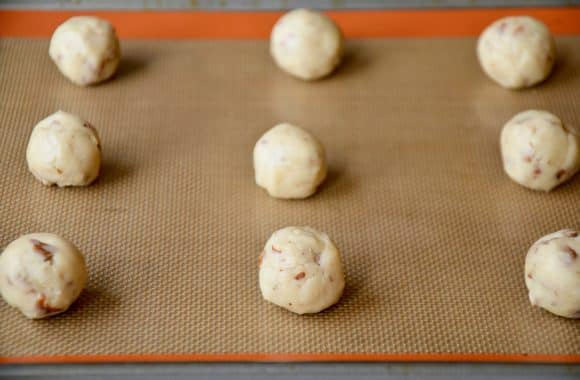 A baking sheet with balls of pecan cookie dough