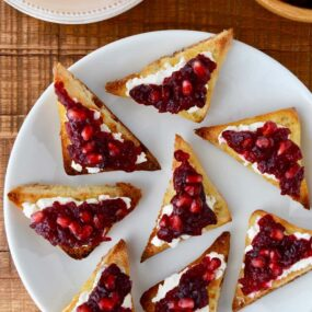 A white plate containing triangular toasts with orange cranberry relish