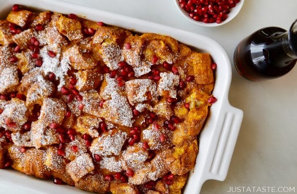 A white baking dish with pumpkin French toast topped with syrup and pomegranate arils