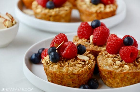 Baked Oatmeal Cups on white plate topped with fresh raspberries and blueberries