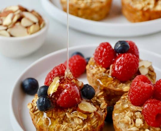 Baked Oatmeal Cups on a white plate topped with fresh raspberries and blueberries being drizzled with warm maple syrup