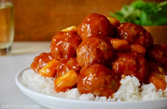 A white plate containing white rice and Sweet and Sour Meatballs with pineapple