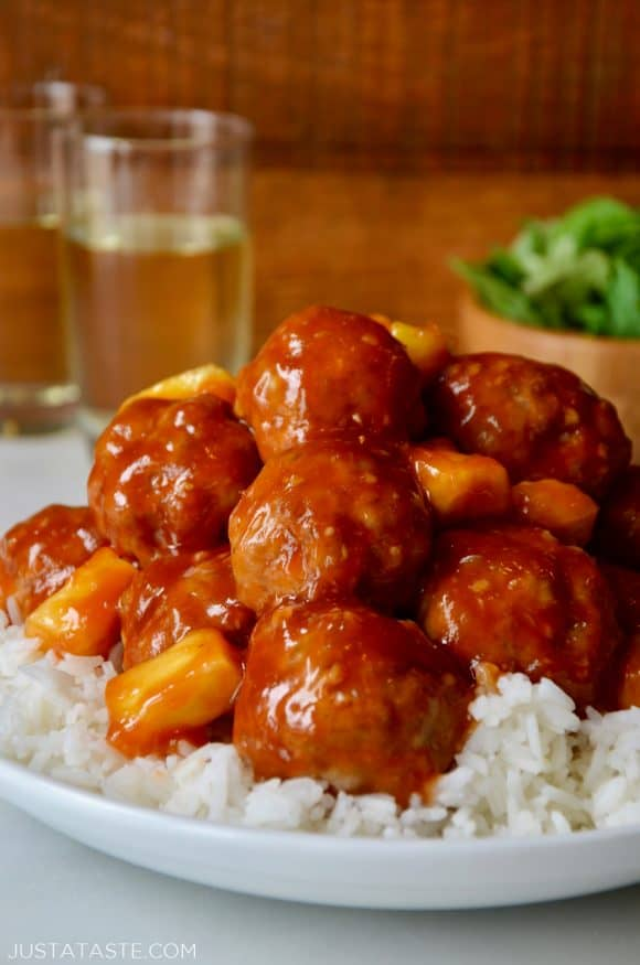 Baked Sweet and Sour Meatballs with pineapple on top of white rice in a white bowl