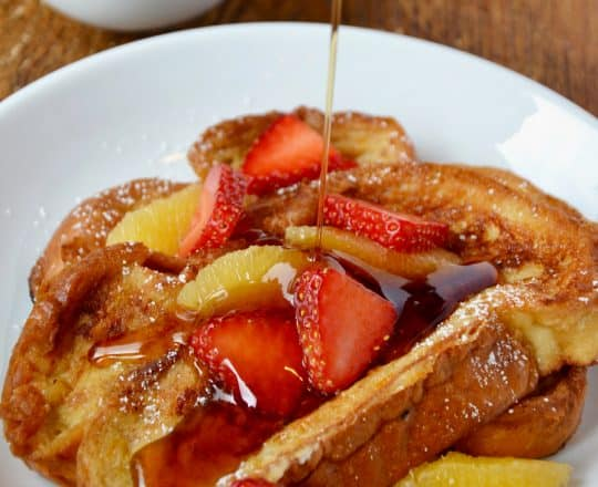 A white plate containing Challah French Toast with syrup being drizzled on top