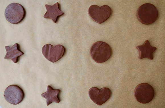 Cut-out circle, star and heart shapes made with chocolate sugar cookie dough