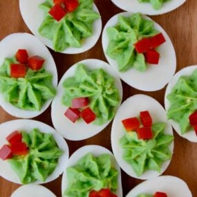 A wooden platter filled with Christmas Deviled Eggs