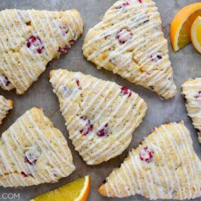 Orange Cranberry Scones on gray background with orange slices