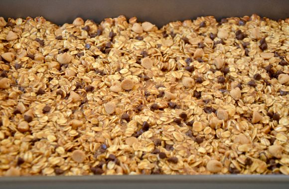 Nonstick baking pan with even layer of Homemade Peanut Butter Granola Bars
