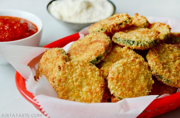 Baked Parmesan Zucchini Chips in white food paper lined red basket with ketchup and mayonnaise in background.