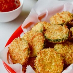 Baked Parmesan Zucchini Chips in red basket lined with white food paper with ketchup and mayonnaise in the background.