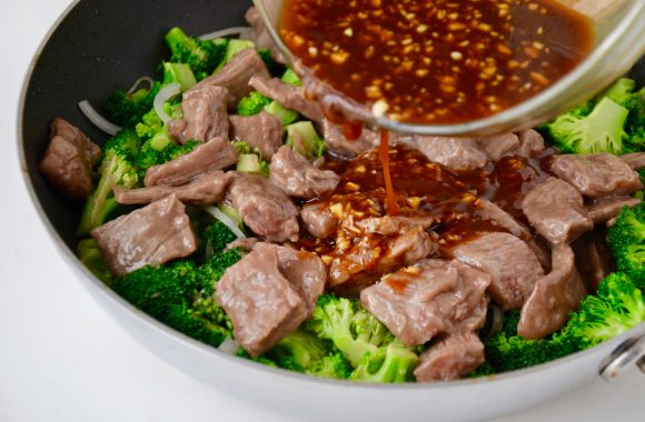 Nonstick sauté pan with broccoli and beef with sauce being poured into pan.