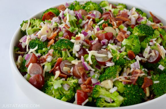 White bowl containing The Best Broccoli Salad with Bacon including crumbled bacon, broccoli florets, sliced almonds, red grapes, shredded mozzarella cheese and red onion.