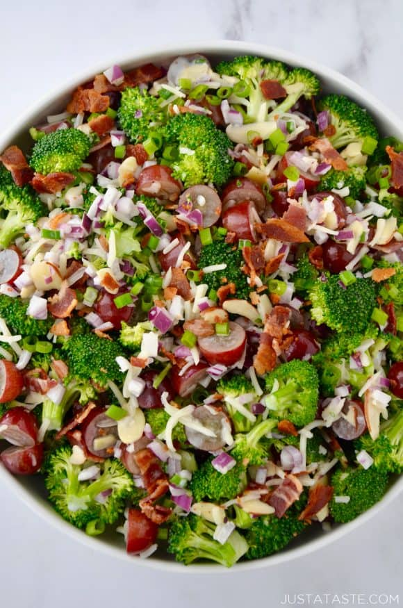 Large white bowl containing The Best Broccoli Salad with Bacon including crumbled bacon, broccoli florets, sliced almonds, red grapes, shredded mozzarella cheese and red onion.