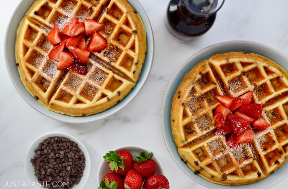Two pale blue plates with Buttermilk Chocolate Chip Waffles topped with strawberries and powdered sugar surrounded by a small glass pitcher of maple syrup, and two small white bowls containing mini chocolate chips and fresh strawberries.