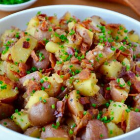 White bowl with Potato Salad with Warm Bacon Dressing next to small white bowl filled with fresh chives and wooden serving spoon and fork.