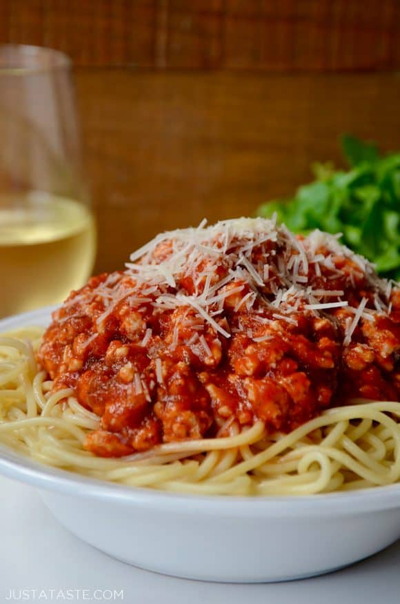 Quick Spaghetti Bolognese with Turkey garnished with shredded Parmesan cheese in white bowl with glass of white wine in background