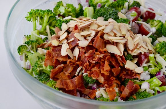Glass bowl containing diced red onion, hredded mozzarella cheese, halved red grapes, chopped scallions, broccoli florets, sliced almonds and crumbled bacon.