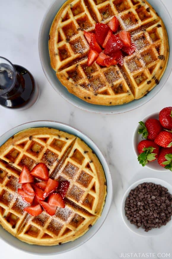 Buttermilk Chocolate Chip Waffles topped with strawberries and powdered sugar on pale blue plates next to a small white bowl filled with chocolate chips, a small glass pitcher with maple syrup and a small white bowl with strawberries.