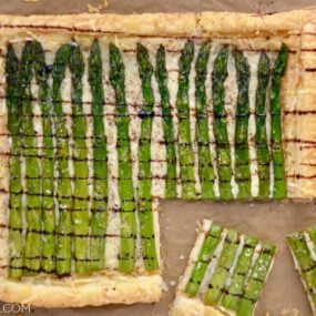 Cheesy Asparagus Tart drizzled with balsamic syrup with corner cut into two pieces on brown paper.