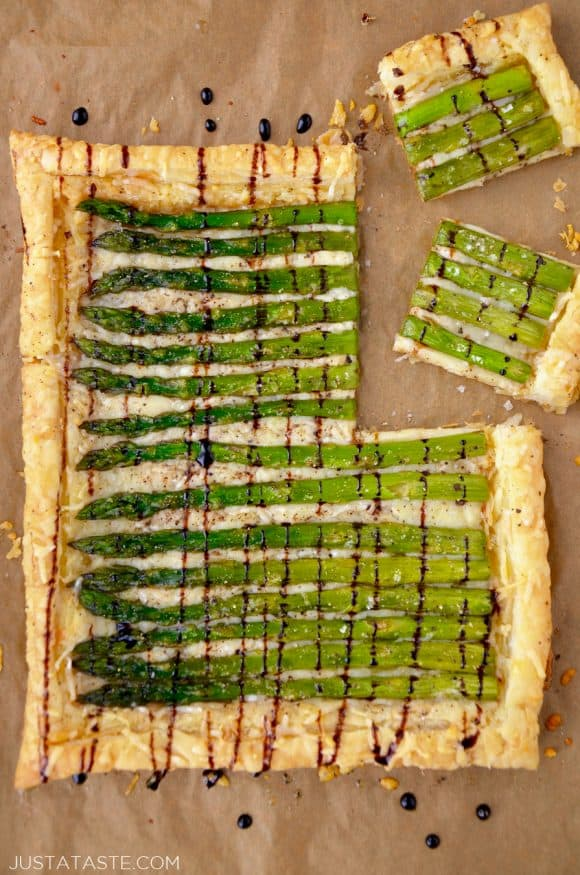 Cheesy Asparagus Tart drizzled with balsamic syrup on brown paper