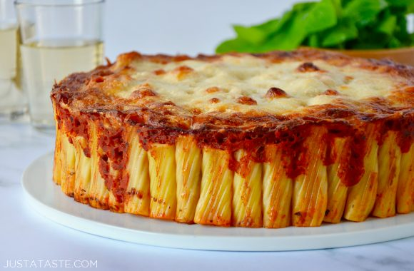 Easy Cheesy Rigatoni Pie on white serving plate with basil and two glasses in the background