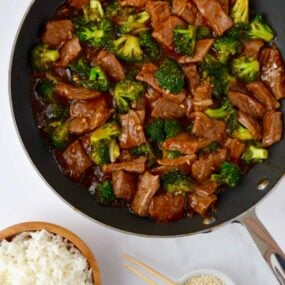 Easy Beef and Broccoli in a nonstick sauté pan, white rice in a small brown bowl and sesame seeds in a small white ramekin with chopsticks resting on top.