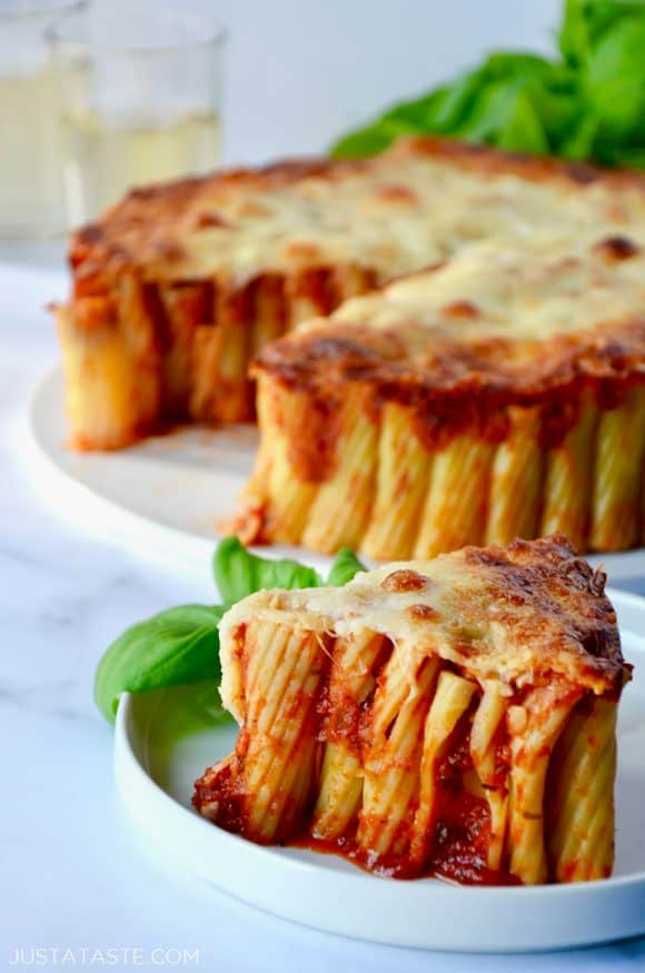 Slice of Easy Cheesy Rigatoni Pie on white plate with basil garnish; Easy Cheesy Rigatoni Pie in background with two glasses of wine and basil beside it