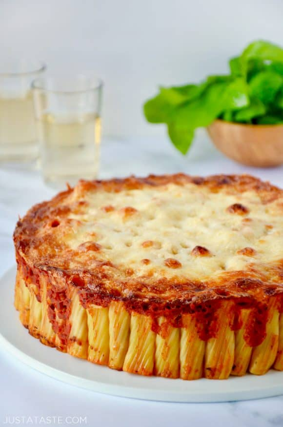 Easy Cheesy Rigatoni Pie on white serving plate with two glasses filled with wine and small wooden bowl with basil in background