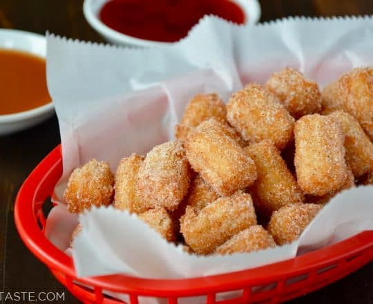 Easy Churro Bites in red basket lined with white food paper with dipping sauces in background.