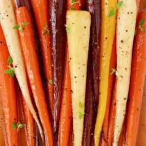 Multi-colored Easy Honey Roasted Carrots on cutting board.