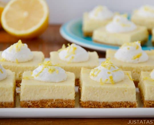 Square-cut Easy Lemon Cheesecake Bars on white plate with cut lemon and more bars on a blue plate in background.