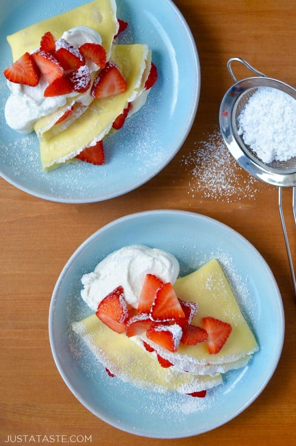 Two pale blue plates with Strawberry Cream Cheese Crêpes topped with fresh strawberries, whipped cream and powdered sugar.