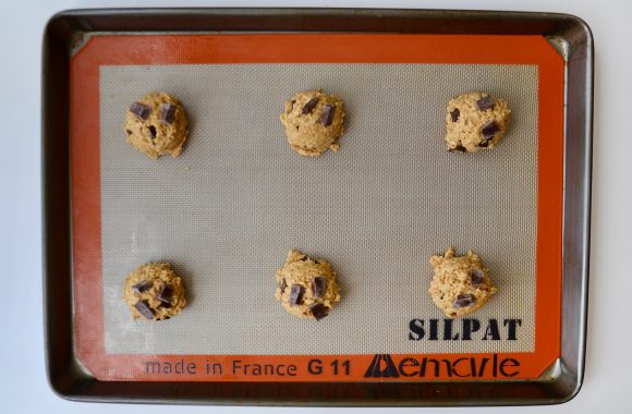Six balls of flourless oatmeal chocolate chip cookie dough on silpat lined baking sheet.