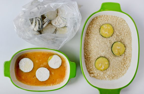 Bag containing flour-coated zucchini, small white and green bowl containing egg mixture and three flour-coated zucchini chips, and one large white and green bowl containing breadcrumbs and three zucchini chips.