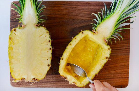 Pineapple cut in half on wooden cutting board with one half hollowed out.