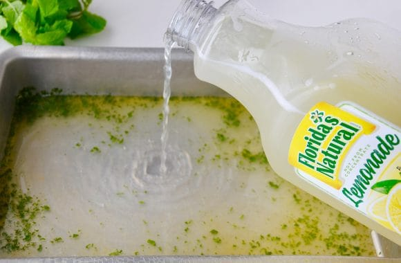 A bottle of Florida's Natural Lemonade being poured into a metal baking pan filled with chopped up mint leaves