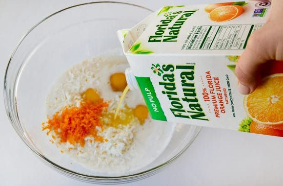A glass bowl containing eggs, orange zest and coconut milk with orange juice being poured in