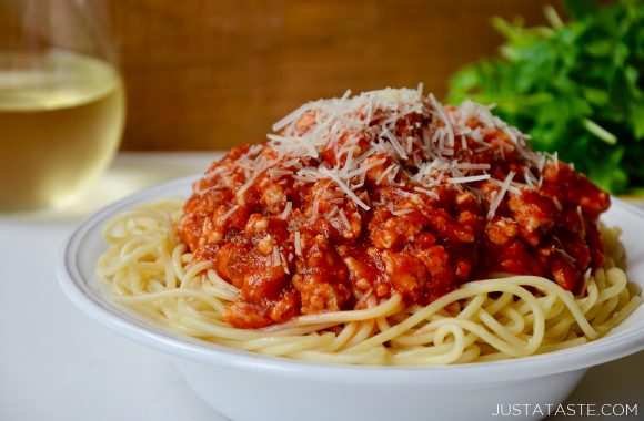 Quick Spaghetti Bolognese with Turkey sprinkled with shredded Parmesan cheese in white bowl; glass of white wine and greens in background.