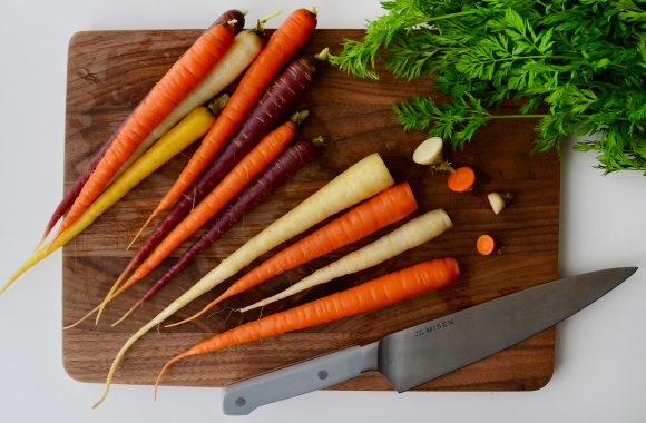 Multi-colored carrots with green tops cut off on wooden cutting board with sharp knife.