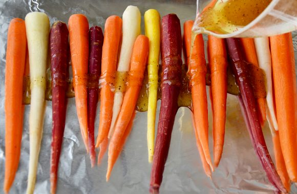 Multi-colored carrots on aluminum foil being drizzled with honey mixture.
