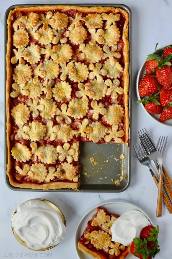 Simple Strawberry Slab Pie with a single serving on a white plate, whipped cream, forks and a bowl of fresh strawberries surrounding it.