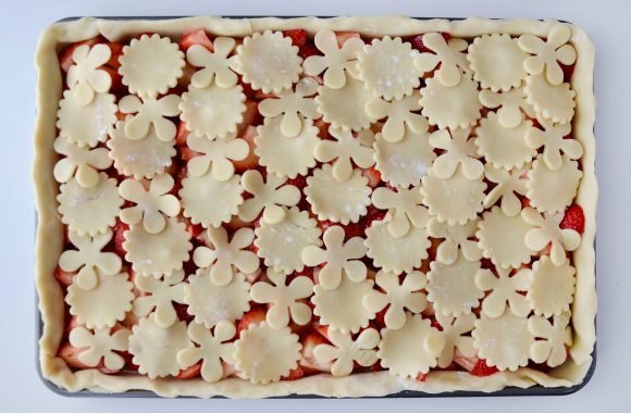 Strawberry slab pie on baking sheet with cutout pie dough shapes prior to baking.
