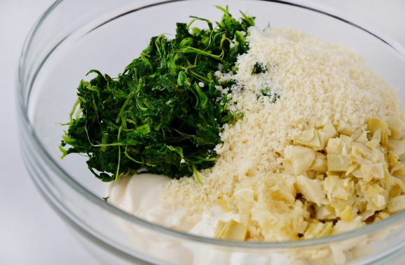 Chopped artichoke hearts, spinach, mayonnaise, sour cream, cream cheese, Parmesan cheese and minced garlic in glass bowl.