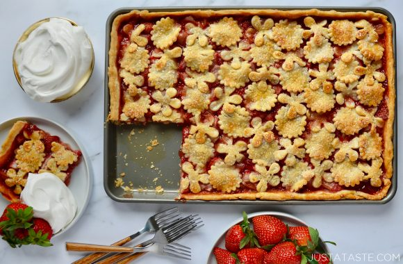 Simple Strawberry Slab Pie with a single serving on a white plate, whipped cream in small bowl, two forks and a bowl of fresh strawberries surrounding it.