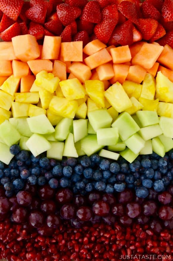 A close-up shot of various fruits arranged in rainbow colors