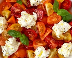 A white bowl containing red, orange and yellow halved tomatoes, burrata and basil