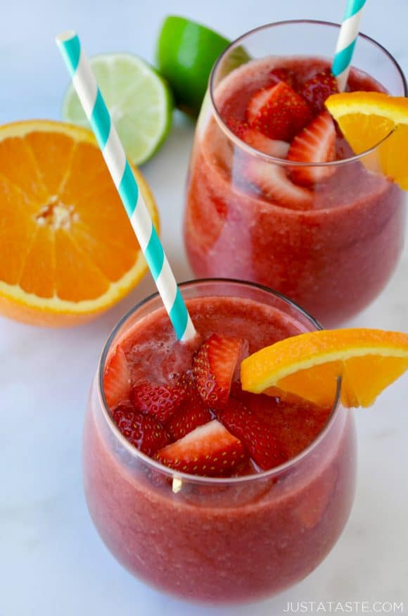 The Best Frozen Sangria topped with fresh strawberries served with an orange slice and straw