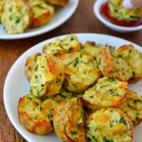 Pile of Cheesy Baked Zucchini Tots on white plate