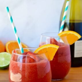 The Best Frozen Sangria with an orange slice and teal stripped straw