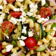 A closeup view of Greek Pasta Salad with Red Wine Vinaigrette that's loaded with sliced cucumbers, halved cherry tomatoes, sliced red onion, black olives and crumbled feta cheese.